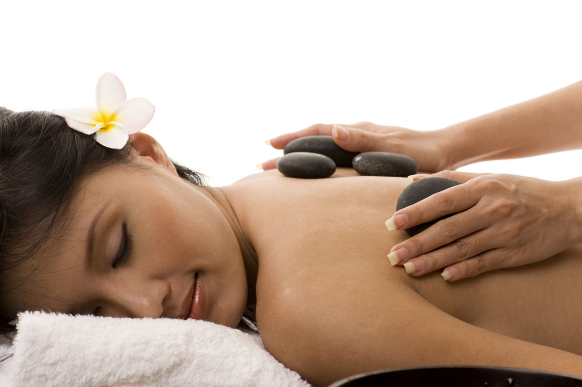 an image of a woman receiving a hot stone massage